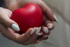 Flickahänder som rymmer röd hjärta, hälsovård, donerar och familjförsäkringbegreppet, världshjärtadagen, dagen för världshälsa, C arkivbild