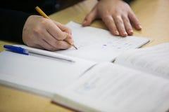 Flickahand som ner skriver ny information i skrivbok arkivbild