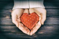 Flickahand som rymmer röd signal för hjärtaformtappning Fotografering för Bildbyråer