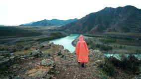 Flickahandelsresande i den orange regnrocken som kommer till kanten av klippan i bergen tillbaka sikt arkivfilmer
