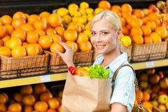 Flickahandpåse med nya grönsaker som väljer apelsiner arkivbild