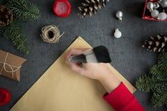 Flickahandstilbokstav till jultomten med bläckpennan på gulingpapper på grå bakgrund med julgarneringar arkivbilder
