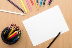 Flickahandteckning Tomt papper och färgrika blyertspennor på trätabellen Arkivfoto