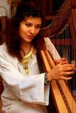 Flickaharpist i den vita klänningen med juvlar som spelar hennes instrument Royaltyfri Foto