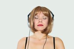 flickaheadphonen lyssnar musik till Arkivfoto