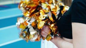 Flickahejaklacksledare som rymmer pompoms under friidrottmästerskap lager videofilmer
