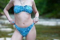 Flickahippier i garneringbohostil och ljusa baddräktställningar mot bakgrunden av floden royaltyfria foton