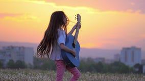 Flickahipster för liten unge som spelar gitarren som en popstjärna i ett maskrosfält utomhus i väg från stadbyggnader lager videofilmer