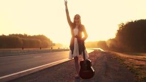 Flickahipster med gitarren som liftar på väglopp på solnedgången Stående av den unga härliga flickan i solglasögon flicka arkivfilmer