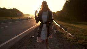 Flickahipster som går ner vägen i strålarna av resningsolen Stående av en ung kvinna på gryning lager videofilmer