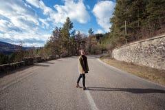 Flickahipsteren står på en bergväg Arkivfoton