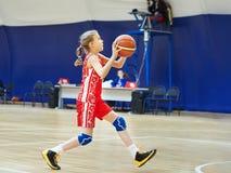 Flickaidrottsman nen i likformign som spelar basket Fotografering för Bildbyråer