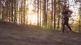 Flickaidrottsman nen på en morgonkörning En muskulös flicka kör stigande på soluppgång i strålarna av solen långsam rörelse lager videofilmer