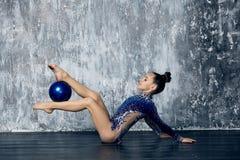 Flickaidrottsman nen som rytmiskt gymnastiskt i en blå dräkt med mousserar, gör övning med sportbollen på golvet arkivbild