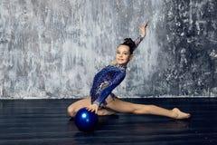 Flickaidrottsman nen som rytmiskt gymnastiskt i en bl? dr?kt med mousserar, g?r ?vning med sportbollen royaltyfri fotografi