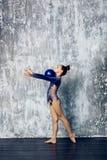 Flickaidrottsman nen som rytmiskt gymnastiskt i en bl? dr?kt med mousserar, g?r ?vning med sportbollen Rymmer bollen i händer fotografering för bildbyråer