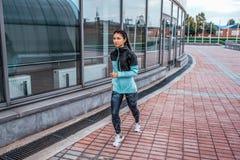 Flickaidrottsman nen, sommarstad Körningar på joggar i ett hopp som spelar sportar på gatan I damasker och omslag Fritt utrymme f arkivbild