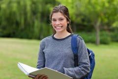 Flickainnehav henne anteckningsbok i en parkera Royaltyfri Fotografi