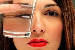 Flickan med ett exponeringsglas av bevattnar Royaltyfri Bild