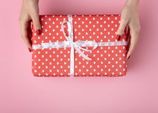 Flickainnehavgåva i händer, asken som slås in i dekorativt papper på en pastellfärgad kulör rosa bakgrund, den bästa sikten, begr arkivfoton