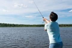 Flickakast som rotera i sjön för att fånga en fisk, bakre sikt royaltyfri bild