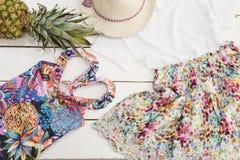 Flickaklädercollage Straw Hat blom- klänning, ananas, tropisk tryckbaddräkt Vit gammal träbakgrund arkivbild