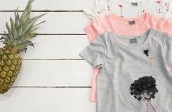 Flickaklädercollage Tre T-tröja, ananas, rosa flamingotryck Vit gammal träbakgrund royaltyfria foton