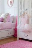 Flickaklänning som hänger på garderob i sovrum Royaltyfri Fotografi