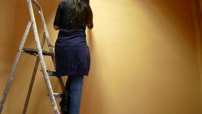 Flickakonstnären målar ett vägganseende på en stege arkivfilmer