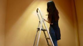 Flickakonstnären målar ett vägganseende på en stege stock video