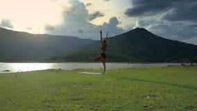 Flickakonturn för den flyg- sikten i yoga poserar på den plana flodbanken lager videofilmer
