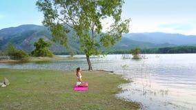 Flickakonturn sitter i yoga poserar på kullar för trädklockasjön arkivfilmer