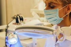 Flickakosmetologen för tillvägagångssättet i skönhetsalongen doktor fotografering för bildbyråer