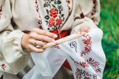 Flickaktigt fritidbegrepp Flicka i traditionell ukrainsk kläder som broderar med en arg metod fotografering för bildbyråer