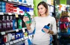 Flickakund som söker efter effektiv munvatten i supermarket Royaltyfri Bild