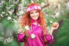 Flickakvinna som är rödhårig i äpple för blomningvårträdgård Royaltyfri Foto
