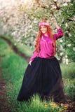Flickakvinna som är rödhårig i vårträdgård royaltyfri foto