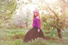 Flickakvinna som är rödhårig i vårträdgård royaltyfri bild