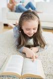 Flickaläsebok med hennes moder som läser tidningen Arkivfoto