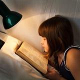 Flickaläsebok på säng på natten Royaltyfri Foto