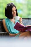 Flickaläseboken dricker kaffe på kafét arkivbilder