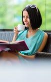 Flickaläseboken dricker kaffe på stången royaltyfri foto