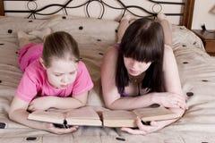 Flickaläsning bokar på säng arkivbild