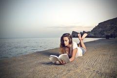 Flickaläsning på stranden Arkivbild