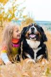 flickalögner bredvid stor hund på höst går arkivfoto