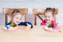Flickalek med deras mat Royaltyfri Foto