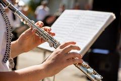 Flickalekar på flöjten Blåsa flöjt i händer av flickan under konserten royaltyfri foto