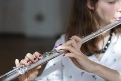 Flickalekar på flöjten Blåsa flöjt i händer av flickan under konserten Yrkesmässig musiker som spelar på flöjten royaltyfri fotografi