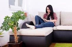Flickaläsebok på soffan Arkivfoto