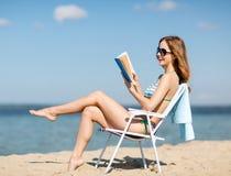 Flickaläsebok på strandstolen Royaltyfria Foton